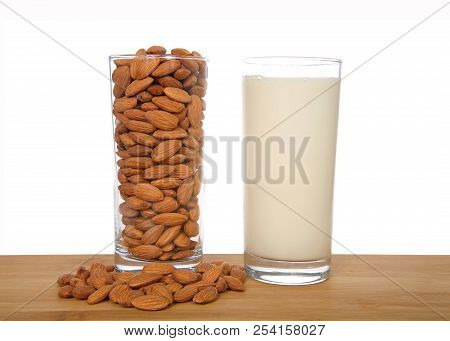 Glass Of Almond Milk Next To Glass Of Whole Almonds On A Wood Table With Raw Almonds, Isolated On Wh