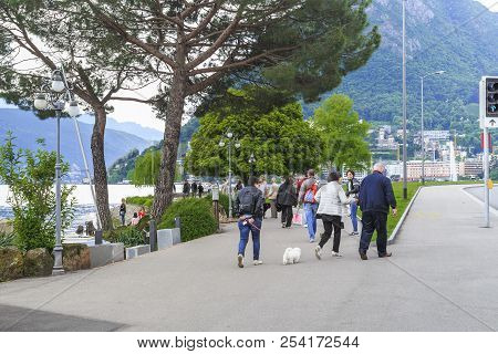 Lugano, Switzerland - May 12, 2018: These Are Unidentified People On The Shore Of Lake Lugano On A D