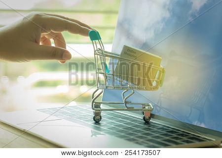 Hand Pushes Cardboard Box With Online Shopping Text In Blue Trolley On Laptop Keyboard Which Has Clo