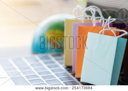 Colorful Shopping Paper Bag On Laptop Keyboard With Globe Nearby. Consumer Can Buy Product Directly