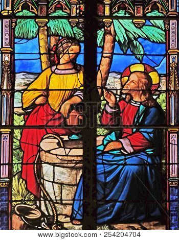 PARIS, FRANCE - JANUARY 10: Jesus and Samaritan woman at the fountain, stained glass window in the Saint Eugene - Saint Cecilia Church, Paris, France on January 10, 2018.