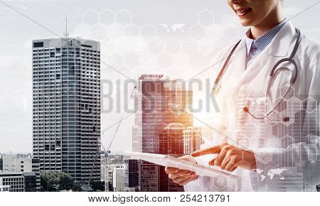 Double Exposure Of Young Woman Doctor In White Medical Suit Touching Tablet With Her Finger And City