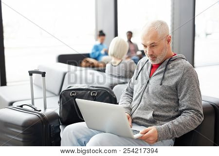 Adult businessman sitting with luggage and browsing laptop in hall of airport