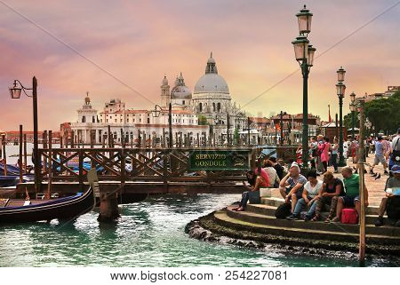 Venice, Italy, Jun 8, 2018: Tourists Sitting On The Steps Near Gondolas With Basilica Di Santa Maria