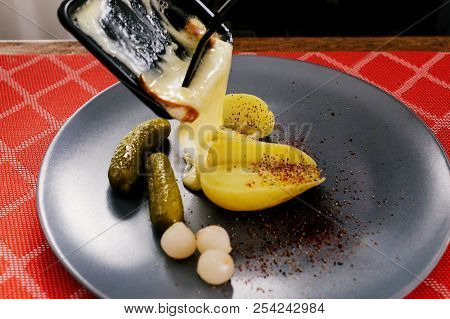 Swiss Traditional Dish Called Raclette Including Steamy Potatoes, Melted Cheese And Pickles Eaten At