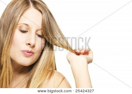 impishly blonde woman playing with her hairs