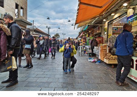 JERUSALEM, ISRAEL - DECEMBER 29, 2016: boy takes pictures of buyers at Mahane Yehuda market in Jerusalem.  More than 250 traders sell fresh fruits and vegetables, baked products, fish, meat and others