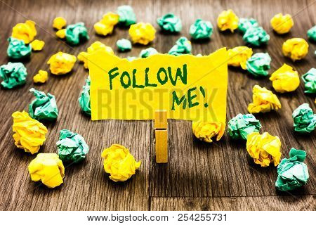 Writing note showing Follow Me. Business photo showcasing Inviting a person or group to obey your prefered leadership Clothespin holding yellow note paper crumpled papers several tries. poster
