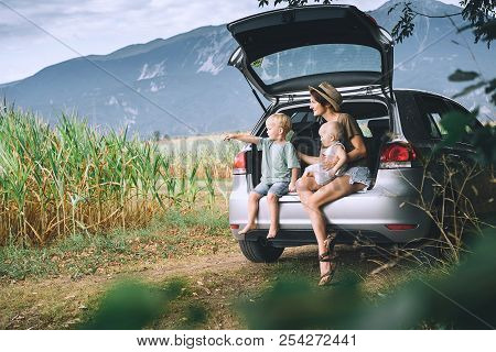 Mother And Children Sitting In An Open Car Trunk And Watching On Nature And Countryside. Family In R