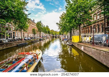 Amsterdam, Netherlands - October 1 2017: A Red Tourist Boat Travels A Picturesque Canal In Amsterdam