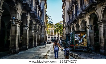 Barcelona, Spain - September 27 2016: A Woman Holds The Hand Of A Young Boy In The Gothic Quarter Of
