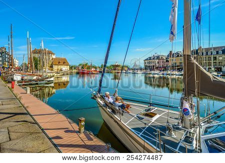 Honfleur, France ; September 17 2017: A Retired Couple Relax On A Sailboat In The Picturesque Old Pi