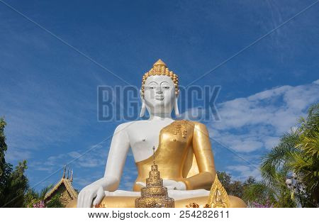 Statue Buddha Sitting On Blue Sky Background