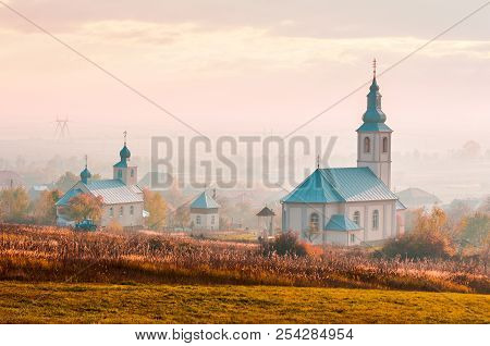Catholic And Orthodox Churches At Foggy Sunrise. Lovely Countryside Scenery In Autumn. Creative Toni