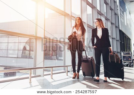 Two Smiling Business Partners Going On Business Trip Carrying Suitcases While Walking Through Airpor