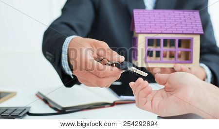 Real Estate Agent In Suit Holds House Model In One Hand And In The Second Hand Holds Out The Keys Of