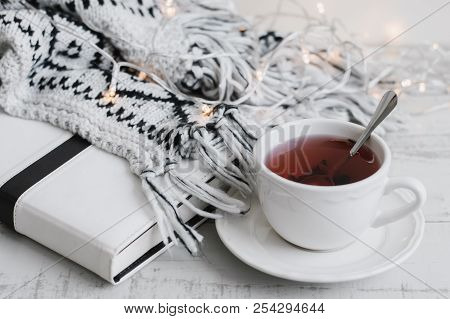 Red Hibiscus Tea In A White Cup, White Book (or Diary, Planner), Lights On Wooden Background. Tea Br