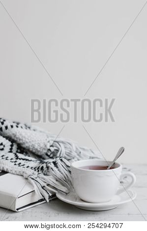 Vertical Background With White Cup Of Red Tea, Book And Knitted Blanket On Wooden Table, Copy Space.