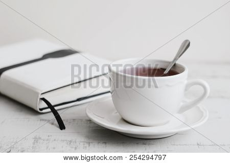 Hibiscus Tea In White Cup And White Book On Wooden Table. Tea Break. Reading, Learning Or Planning D