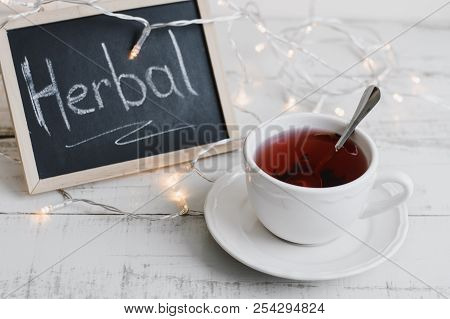Red Hibiscus Tea In A White Cup, Lights For Home Decoration And Blackboard With Text