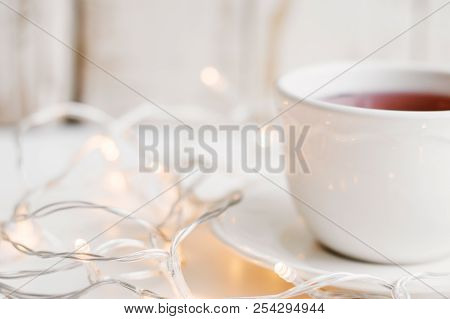 Cup With Red Hibiscus Tea And Yellow Lights For Home Decoration. Cosy Atmosphere