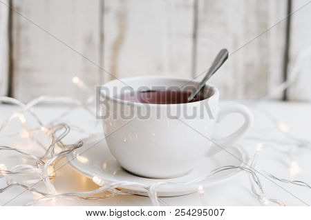 Red Hibiscus Tea In A Small White Cup And Many Yellow Lights For Home Decor On White Table