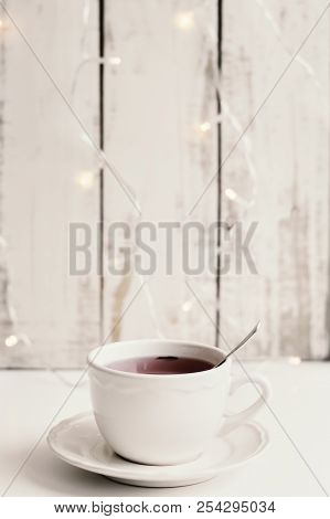 Red Hibiscus Tea In A White Cup On White Table, Wood And Lights For Decoration As Background. Tea Br