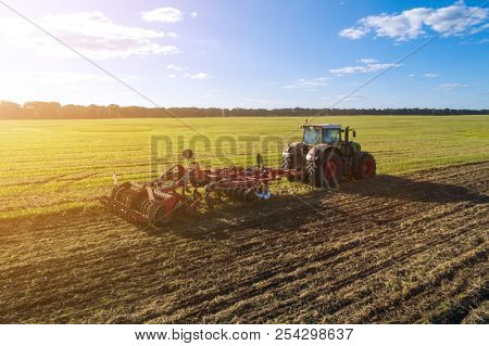 Agricultural tractor plowing the field at sunset. Agricultural machinery in field