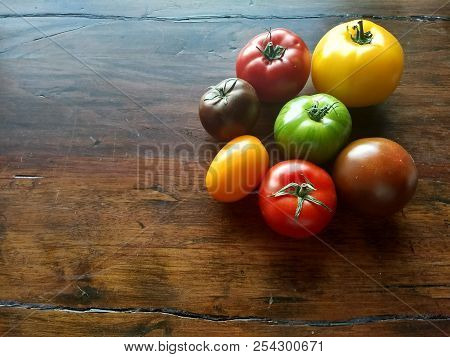 A Colorful Assortment Of Heirloon Tomatoes On A Wooden Table