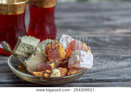 Turkish joys with different nuts are a glass of tea and a spoon. Eastern sweets. Traditional Turkish delight (Rahat lokum) on a wooden background. Side view. poster