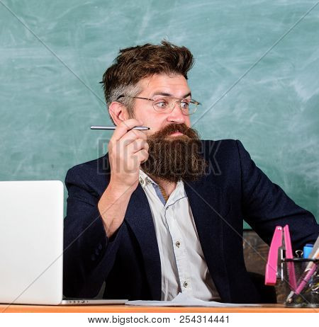Not Sure In Knowledge. Examiner Full Of Doubts Sit At Table Chalkboard Background. School Exam Conce
