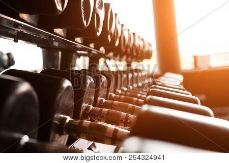 Black Dumbbells Set. Close Up Photo Various Metal Dumbbells On The Rack In Sport Fitness Center Agai
