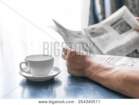 A Man Reading Newspaper And Drinking Coffee Sitting In Cafe Or At Home Next To Kitchen Window At Sun