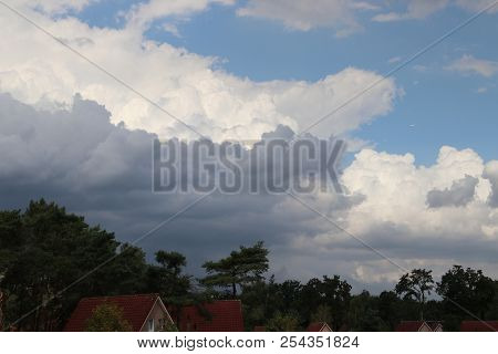 Dark Cumulonimbus Clouds Above Trees And Houses To Become Bad Weather In The Netherlands.