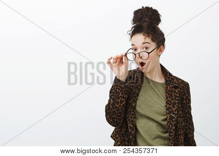 Waist-up Shot Of Impressed Surprised Curly-haired Attractive Female In Leopard Coat, Taking Off Glas
