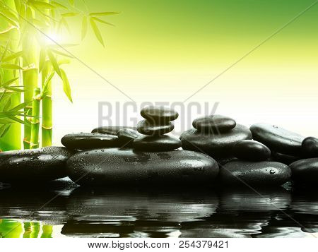 Zen Basalt Stones With Green Bamboo On Water. Spa And Wellness Concept.
