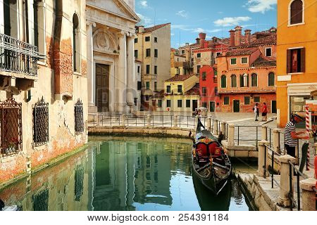 Venice, Italy, Jun 8, 2018: A Charming View Of Venetian Street Corner With Canal, Locals, Gondola An