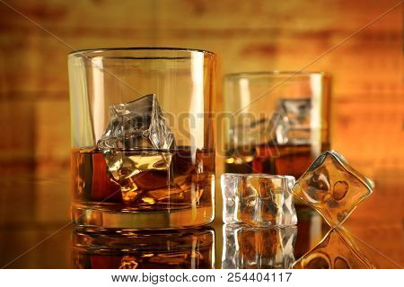 Two Whiskey Or Rum Glasses With Ice Cubes