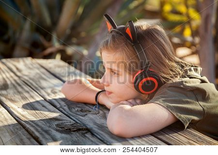 A Young, Blond Girl Sits With Her Chin On Her Hands At A Picnic Table In The Desert With Late Aftern
