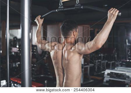 Man Is Exercising Latissimus With Equipment Indoors