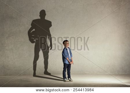 American Football Champion. Childhood And Dream Concept. Conceptual Image With Boy And Shadow Of Fit
