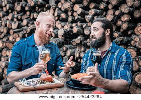 Two Bearded Businessmen Having Informal Meeting Drinking Beer