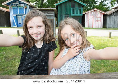 Two Girls Sister Play Outdoor In Fun Make With Phone Smartphone A Selfie Picture