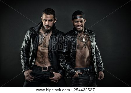 Two Models With Tattooed Chests. Bikers In Leather Jackets. Rock Band Isolated On Black Background.