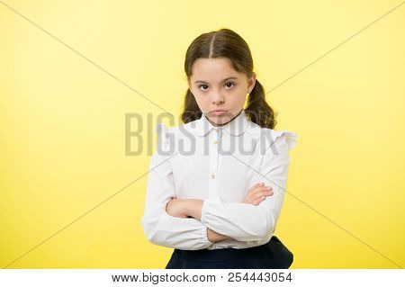 Disagreement And Stubbornness. Girl School Uniform Serious Face Offended Yellow Background. Kid Unha