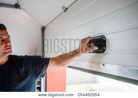 Man Opens White Pvc Garage Door Manually