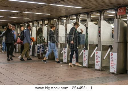 New York, Usa - May 13, 2018: Commuters Going Through The Turnstiles In A Subway Station In New York