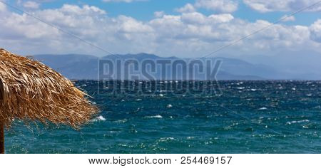 Straw umbrella closeup, windy beach and stormy sea and sky background