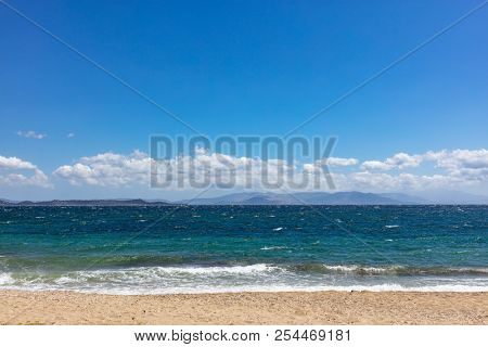 Windy sandy beach, rough sea with waves, blue sky with clouds background