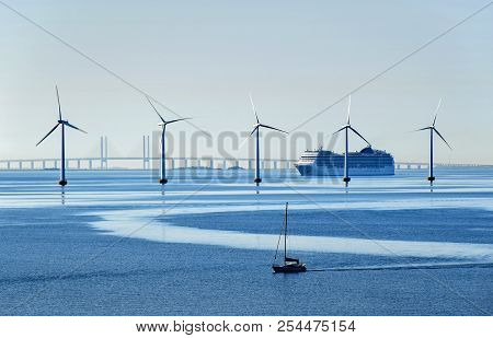 A Very Large Passenger Ship And A Small Sailboat Pass Offshore Wind Turbines Near The Oresund Bridge